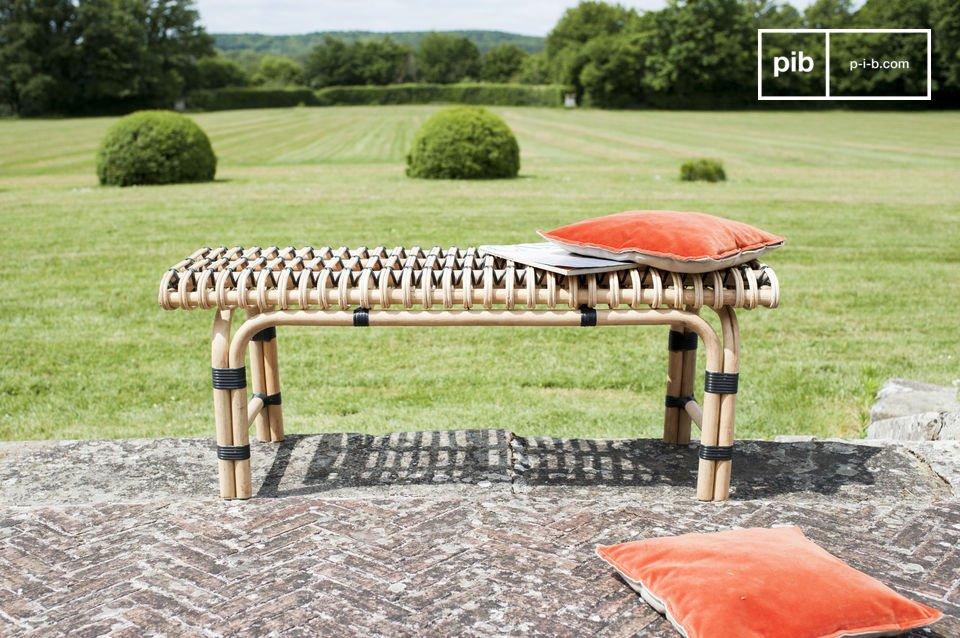 Der durch drei senkrechte Holzstangen verstärkte Sitz weist schöne geometrische Motive aus Rattan