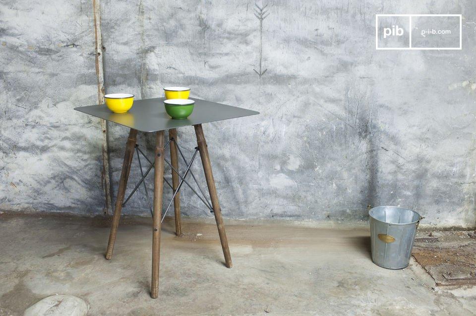 Unter der metallischen Tischplatte vereinen sich die vier Füße dieses Bistrotisches und