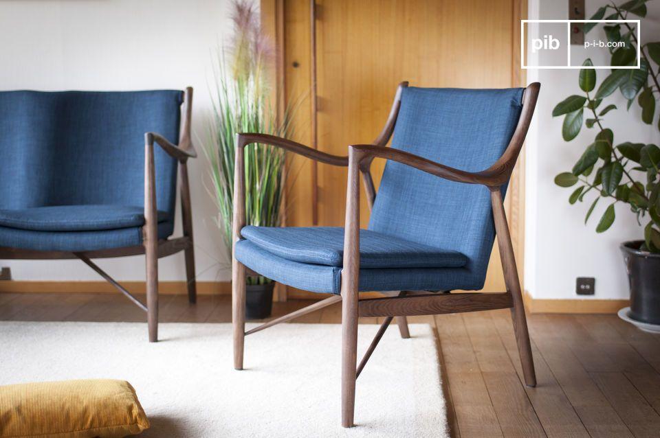 Die dezente Eleganz eines blauen und hölzernen Sessels mit Retro-Inspiration