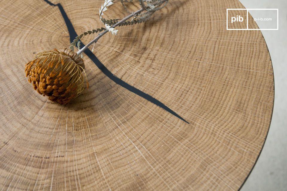 Der natürliche Riss im Holzstück ist mit Schwarz gefüllt und erinnert an die Farbe des Fußes