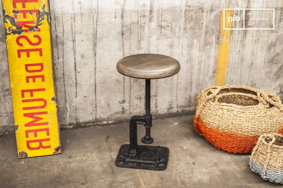 Die helle Sitzfläche kontrastiert mit der schwarzen Farbe des gusseisernen Tischbeines: Die Form des Tischbeines ist besondres originell, da sie an eine Klemmzwinge erinnert