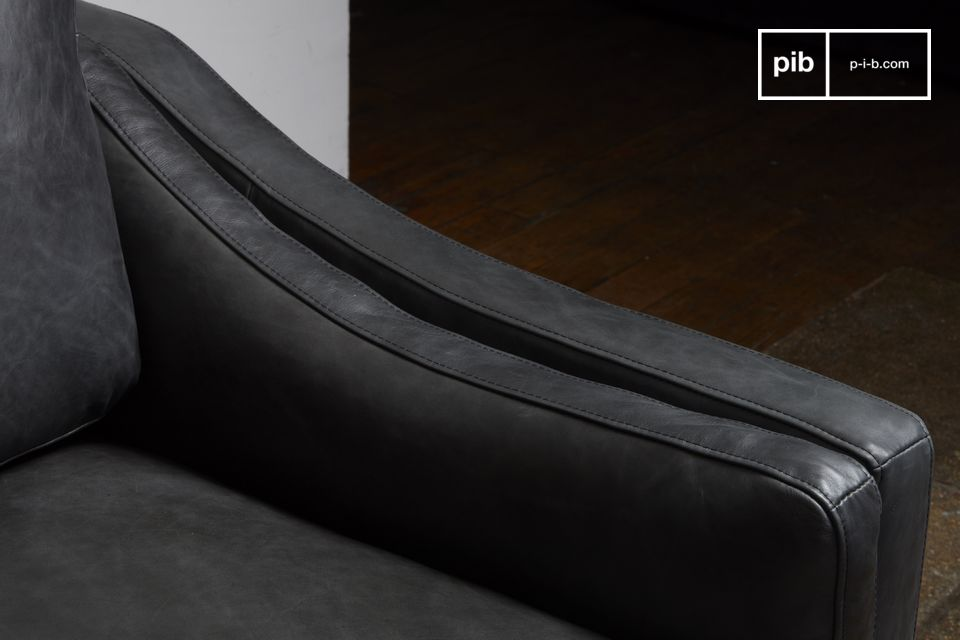 Das Sofa bietet feste Armkissen, die sich harmonisch an die leicht geschwungene Form anlehnen