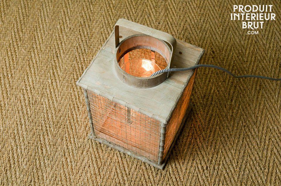 Diese originelle Laterne aus hellem lasierten Holz besteht aus einem Glasbehälter als Windschutz