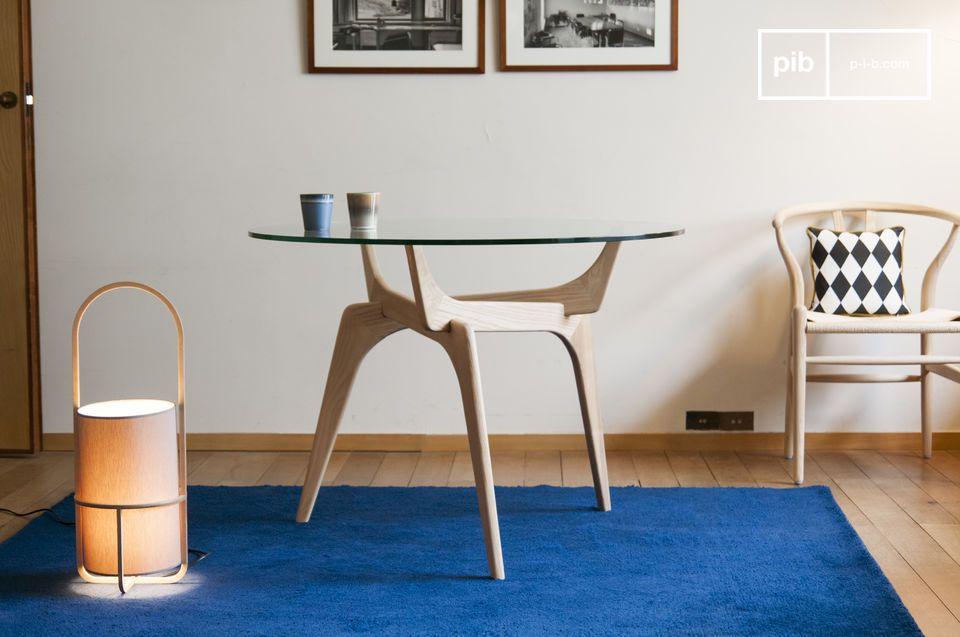 Die Retro-Linien eines kunstvollen runden Tisches aus Glas und Holz