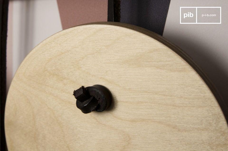 Die Holzscheiben sind auf der Leiste mittels Lederschlaufen angebracht und geben einen