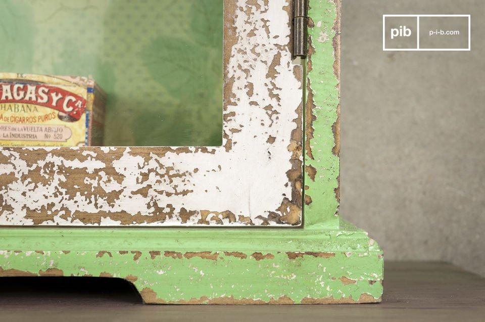 Durch seine grüne Verkleidung mit Blumenmotiven und das von Hand patinierte Holz verleiht